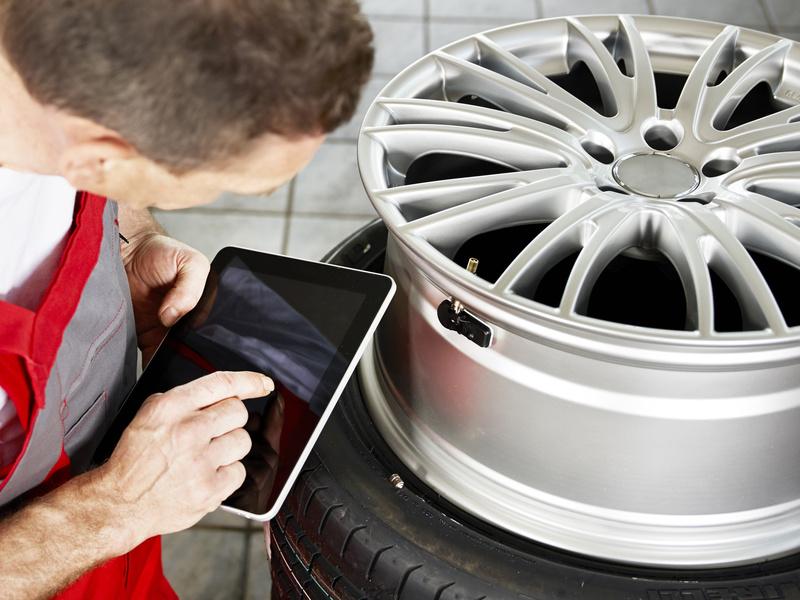 Mechanic fits tyre pressure monitoring system with tablet